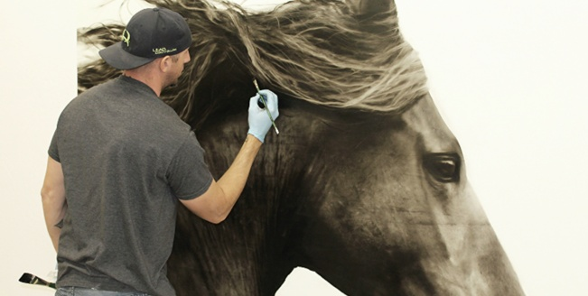 Photo of Kenneth Peloke painting a horse.